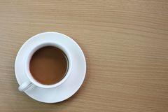 white coffee mug placed on a brown wooden table royalty free stock image