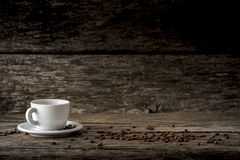 White coffee mug on a plate placed on a rustic wooden boards wit Stock Image