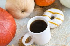 White coffee mug among the red pumpkin, a donut with frosting Royalty Free Stock Photo