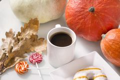 White coffee mug among red pumpkins, Donat with icing, lollipops Stock Image