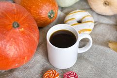 White coffee mug among the red pumpkins, donut with icing, candy Stock Photography