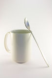 White Coffee Mug with Spoon. Tall white coffee mug with long spoon on a white background Stock Photo
