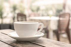 A white coffee mug stands on a wooden table in an outdoor coffee shop. light blurred background. close up. stock photo