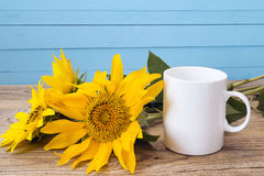 White coffee mug with sunflowers on a blue background. Stock Photos