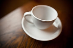 White coffee mug on white plate Stock Images