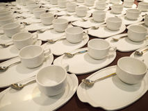 White Coffee/tea cups for catering. White Coffee/tea cups with saucers and spoons ready for buffet or catering event Royalty Free Stock Photo