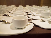White Coffee/tea cups for catering. White Coffee/tea cups with saucers and spoons ready for buffet or catering event Royalty Free Stock Photography