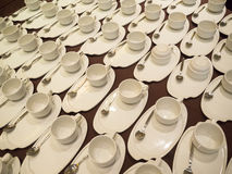 White Coffee/tea cups for catering. White Coffee/tea cups with saucers and spoons ready for buffet or catering event Stock Photo