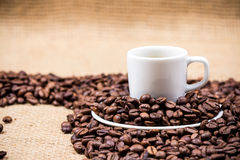 White coffeecup on coffeebeans. White coffeecup and plate on coffeebeans on gunny background Stock Photos