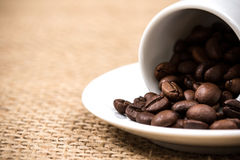 White coffeecup and plate with spilled coffeebeans. On gunny background Stock Photography