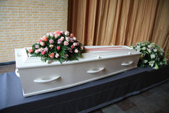 White coffin with pink sympathy flowers Royalty Free Stock Photos