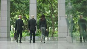 White collar businesspeople walking exiting modern building. White collar corporate business people with coffee or bag in hand walking out of building saying