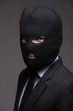 White collar crime. Portrait of businessman in black balaclava l Stock Photo
