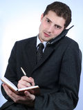White-collar worker phone and writing. Over sky-blue background Stock Photography