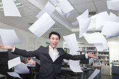 White-collar worker throwing white sheets in air in office Royalty Free Stock Images