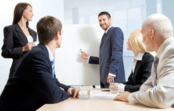 White collar workers at a meeting. A businessman making a report and four people listening to him royalty free stock photos