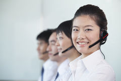 White Collar Workers in a row with headsets Royalty Free Stock Images