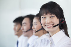 White Collar workers in a row with headsets Royalty Free Stock Photo