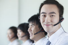 White Collar workers in a row with headsets Royalty Free Stock Image