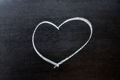 White coloe chalk drawing as heart shape on blackboard background with copy space. Drawn, marriage, design, love, chalkboard, romance, romantic, icon stock photos