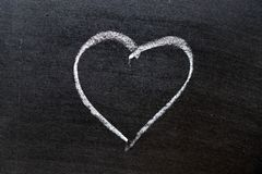 White coloe chalk drawing as heart shape on blackboard background with copy space. Drawn, marriage, design, love, chalkboard, romance, romantic, icon royalty free stock photography