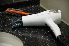 Hair dryer. White color hair dryer with round brush on a washstand stock images