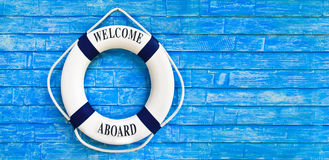 White color Life buoyancy with welcome aboard on it hanging on b. Lue wall. had space on right side for your text Royalty Free Stock Images
