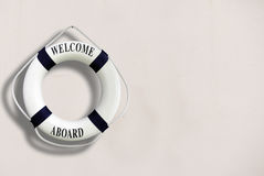 White color Life buoyancy with welcome aboard on it hanging on w. Hite concrete wall.had space on right side for your text Stock Images