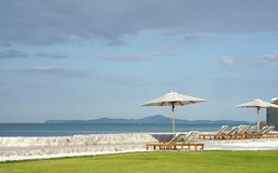 White color recliner beach seating with white parasol facing the Stock Photography