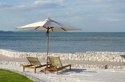 White color recliner beach seating with white parasol facing the Stock Image