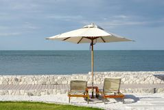 White color recliner beach seating with white parasol facing the Royalty Free Stock Images