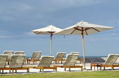 White color recliner beach seating with white parasol facing the Royalty Free Stock Photo