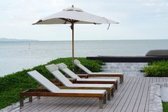 White color recliner beach seating with white parasol facing the Stock Photos