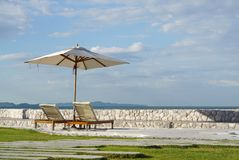 White color recliner beach seating with white parasol facing the Royalty Free Stock Photography