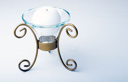 White color sphere shaped candle in a metal holder. White color sphere shaped candle in a luxurious glass and metal holder stock image