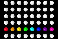 White and colored balls on a dark background. Royalty Free Stock Image