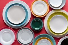 White and colorful plates of different sizes. On red background royalty free stock image