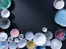 White and colorful tableware in different designs and sizes on black background, photographed from above in daylight. White and coloured tableware in different royalty free stock images