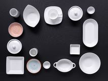 White and colorful tableware in different designs and sizes on black background, photographed from above in daylight. White and coloured tableware in different stock photos