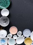 White and colorful tableware in different designs and sizes on black background, photographed from above in daylight. White and coloured tableware in different royalty free stock photography