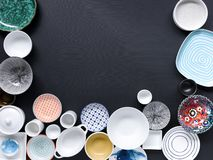 White and colorful tableware in different designs and sizes on black background, photographed from above in daylight. White and coloured tableware in different stock images