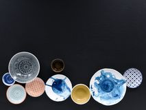White and colorful tableware in different designs and sizes on black background, photographed from above in daylight. White and coloured tableware in different royalty free stock photos