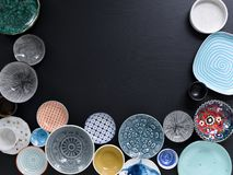 White and colorful tableware in different designs and sizes on black background, photographed from above in daylight. White and coloured tableware in different stock photography