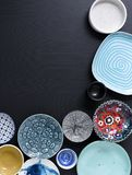 White and colorful tableware in different designs and sizes on black background, photographed from above in daylight. White and coloured tableware in different royalty free stock photo