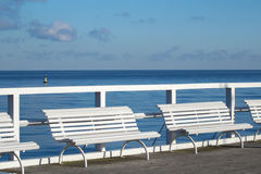 White comfort benches on sea walking pier Royalty Free Stock Photos