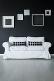 White comfortable sofa. On panel floor with checkered black pillows against black wall with frames Royalty Free Stock Photos