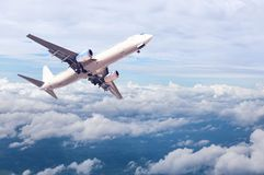 White commercial airplane flying away in to sky high altitude above the white clouds Stock Images