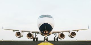 White commercial airplane standing on the airport runway at sunset. Front view of passenger airplane is taking off. White commercial airplane standing on the royalty free stock photography