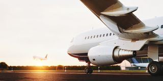 White commercial airplane standing on the airport runway at sunset. Passenger airplane is taking off. White commercial airplane standing on the airport runway Stock Photography