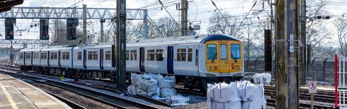 A white commuter train. Pulls into the station, on a sunny winter day Royalty Free Stock Photography